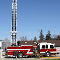 A custom Toyne Aerial fire truck in action with an extended ladder.