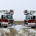 Side view of two Toyne Aerial fire trucks in winter.