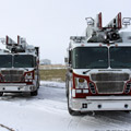 Front view of two Toyne Aerial fire trucks in winter.